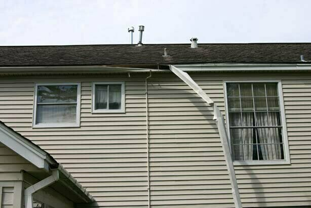 Gutter repairs are needed! A gutter has completely detached from a house.