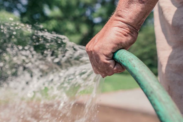 man watering and cleaning for summer gutter guards